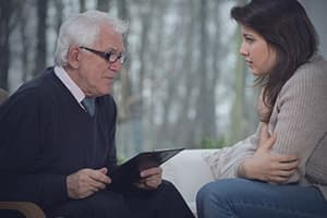 Medically trained therapist helping younger woman