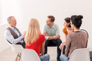 People sitting in chairs in circle depicting inpatient group therapy