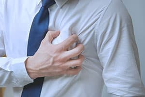 man having heart problems grasping chest