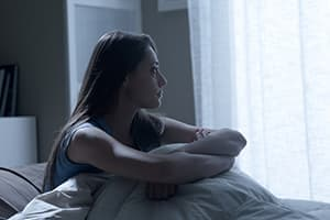 woman depressed sitting on bed
